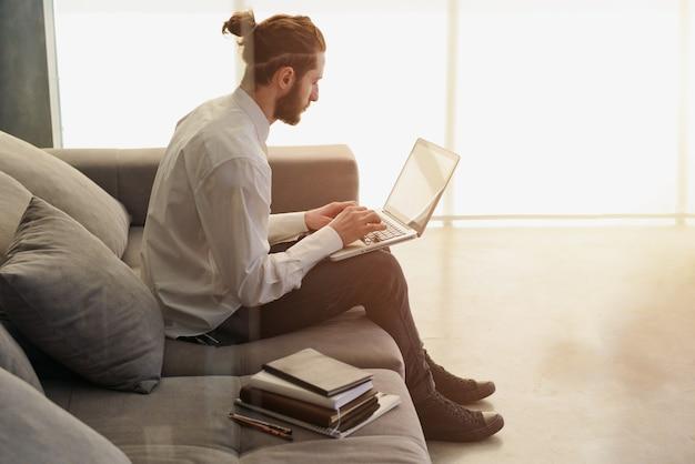 Деловой человек работает на диване со своим ноутбуком. он в умной работе