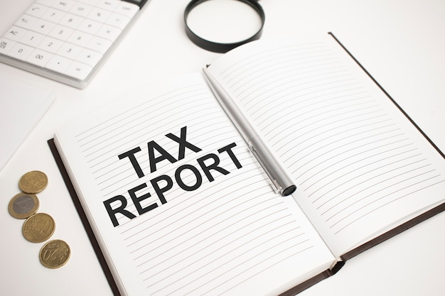 Business accessories, calculator, coins, reports and magnifier glass with text tax report