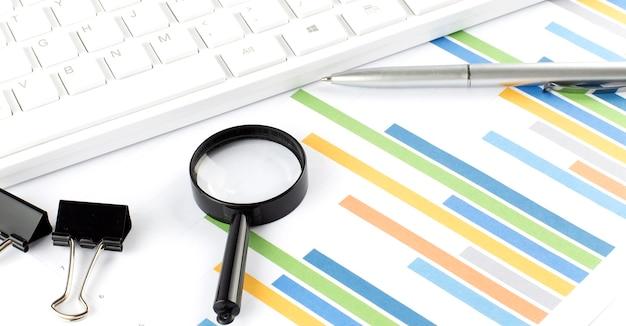 비즈니스 회계사는 흰색 사무실 책상 평면도에 차트와 키보드로 작업