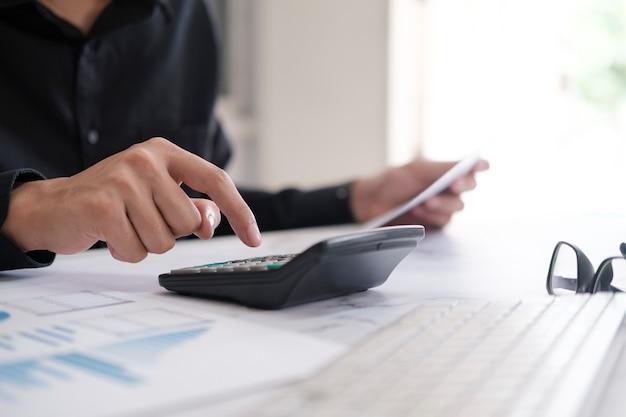 ビジネス会計の概念、コンピューターのラップトップで計算機を使用するビジネスマン、オフィスで予算とローンの紙。