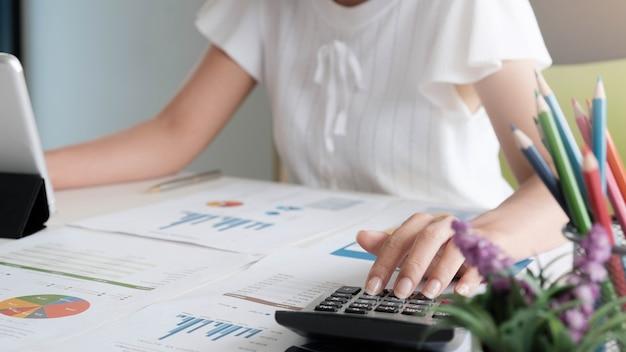 テーブルの作業領域に計算機とビジネス会計の概念の実業家とラップトップ