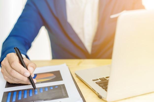 Концепция плана бухгалтерии дела, работая на портативном компьютере настольного компьютера с калькулятором для делать дело, рука бизнесмена работая с портативным компьютером на деревянном консультанте капиталовложений предприятий стола.