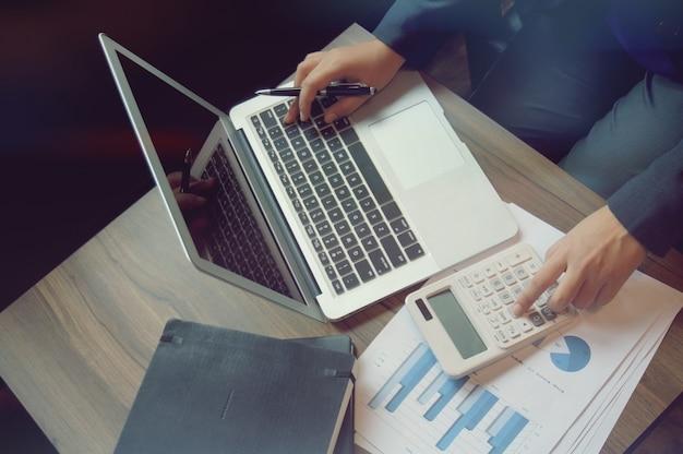 Женщины, работающие в сфере бухгалтерского учета, работают с калькулятором и ноутбуком. концепция финансовых технологий
