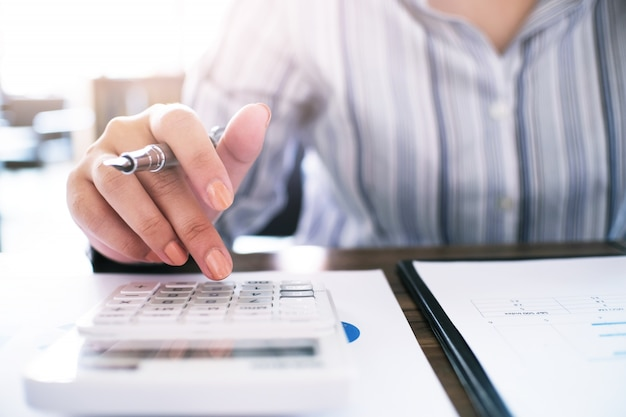 Женщины, работающие в сфере бухгалтерского учета, работают с калькулятором и ноутбуком