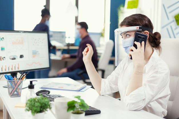 スマートフォンで話しているcovid19の間にフェイスマスクを身に着けている彼女の職場に座っているビジネス管理者。金融会社で社会的距離を尊重して働く多民族の同僚。