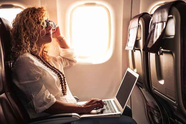 Деловая взрослая красивая кудрявая блондинка путешествует на самолете, подключенном к интернету с современным компьютерным ноутбуком