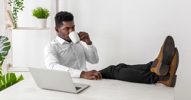 Деловой афро-американский мужчина пьет кофе в офисе