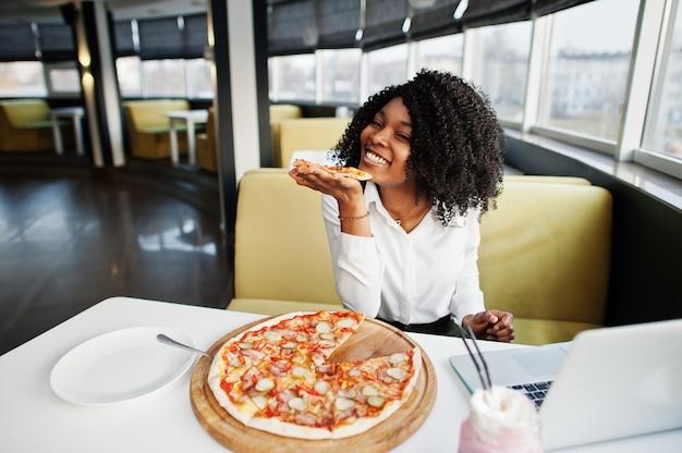 Деловая африканская леди с афро волосами, надевайте белую блузку, сидя за столом, работайте с ноутбуком в кафе, ешьте пиццу и пейте розовый коктейль молочного коктейля.