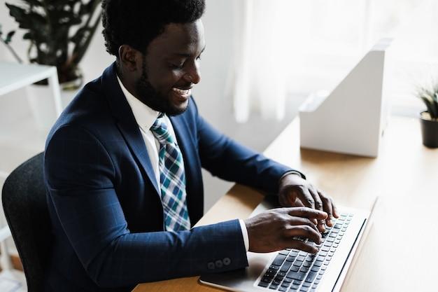 Деловой африканский человек, работающий в современном офисе с помощью портативного компьютера - сосредоточиться на лице