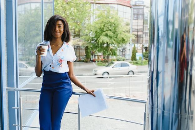 Деловая афро-американская женщина, держащая чашку кофе и файлы