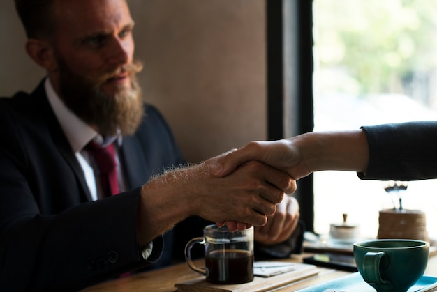 Business agreement handshake at coffee shop