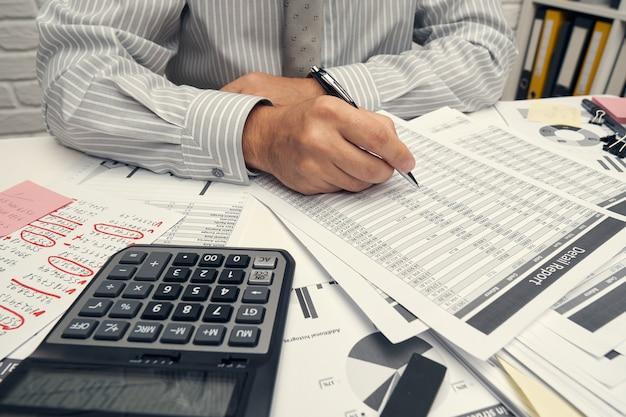 Бизнес-анализ и концепция бухгалтерского учета - бизнесмен, работающий с документом, электронной таблицей, с помощью калькулятора, планшетного пк. офисный стол крупным планом.