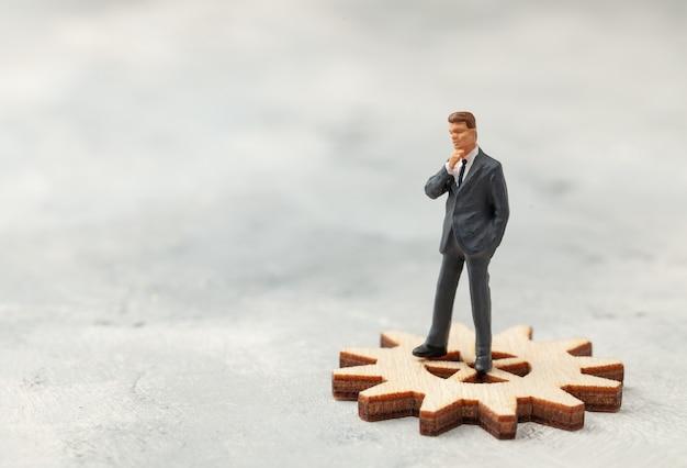スーツを着た会社のビジネスマンの事業分析監査は、ビジネスの象徴としてギアに立っています