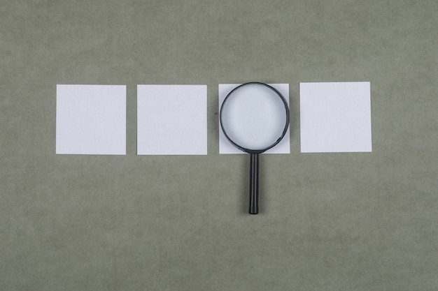 Business analysis concept with sticky notes, magnifying glass on grey surface flat lay.