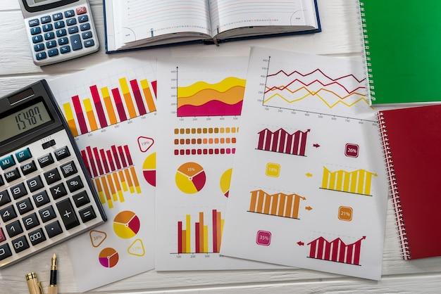 グラフ、計算機、ラップトップを備えたビジネスアナリストの職場