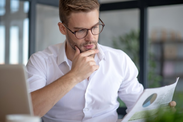 Business analyst. a thoughtful man carefully reading a business report