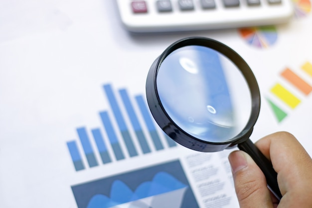 ビジネス分析と統計。株式市場チャートに虫眼鏡を使用するビジネスマン