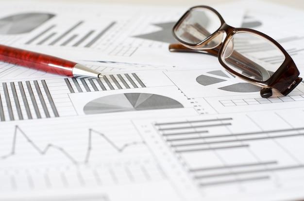 ビジネス分析、グラフ、チャート。紙の概略図。ボールペンとメガネ