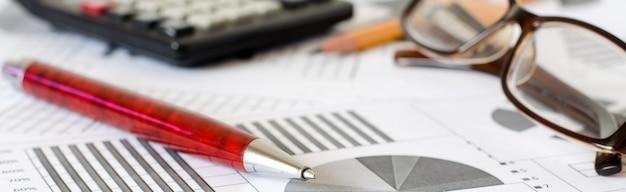 ビジネス分析、グラフ、チャート。紙の概略図。ボールペン、メガネ、電卓