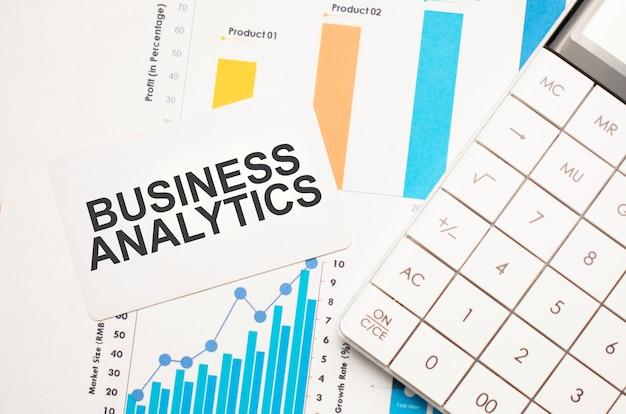 ビジネス分析、テキストの概念。色とりどりの背景の小さな紙に電卓、グラフ、レポート、テキストビジネス分析を備えたオフィスの職場のテーブル。