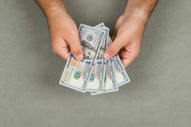 회색 표면 평면에 비즈니스 및 회계 개념 누워. 현금 달러를 고려하는 남자.