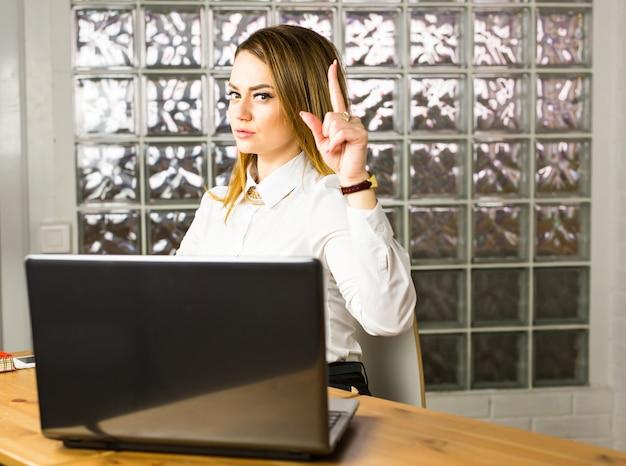 ビジネスと広告のコンセプト-オフィスで彼女の指で魅力的な若い女性