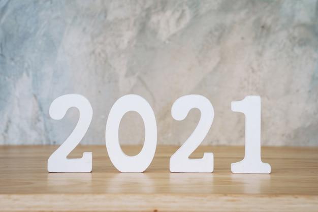 ビジネスとデザインのコンセプト-木製のテーブルに新年あけましておめでとうございますテキストの木製番号2021。