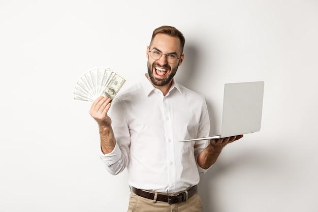 ビジネスとeコマース。お金のドルとラップトップを保持し、オンラインで作業し、白い背景の上に立っている興奮した実業家。