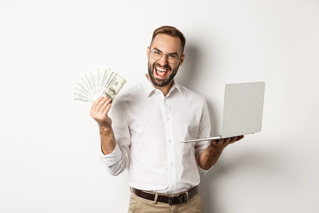 Бизнес и электронная коммерция. возбужденный бизнесмен, держащий деньги, доллары и ноутбук, работает в интернете, стоя