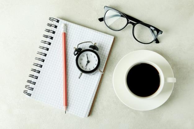 白い織り目加工のテーブルに目覚まし時計とビジネスと教育の概念