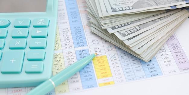 ビジネスと金融の概念。職場での財務計算、計算機、ドルのクローズアップ。