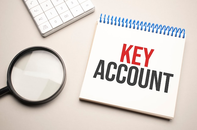 비즈니스 및 금융 개념입니다. 탁자 위에는 돋보기, 계산기, key account라고 적힌 노트북이 있습니다.
