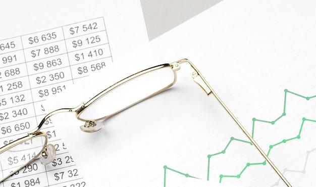 白い表面に眼鏡とペンを使ったビジネスと財務のチャート