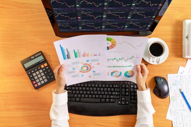 비즈니스 및 금융 개념 보고서 차트를 들고 비즈니스 여성의 상위 뷰 손. 컴퓨터 화면에 차트 및 분석 그래프를 들고 사업 사람들의 손에.