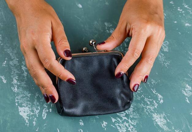 ビジネスと金融の概念。女性は小銭入れを開きます。