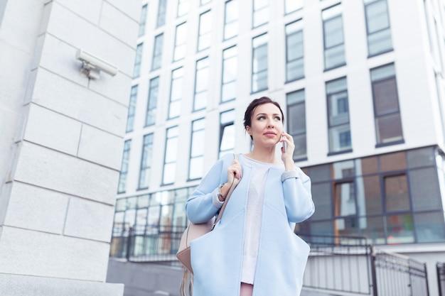 비즈니스 및 프리랜서 개념입니다. 사무실 건물을 배경으로 거리에서 휴대전화로 일하는 젊은 여성