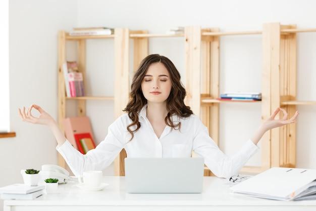 ラップトップの近くのビジネスと健康の概念の肖像画の若い女性が1分間休憩時間を取っているラップトップのオンラインヨガのクラスの前にオフィスの机で瞑想を練習します