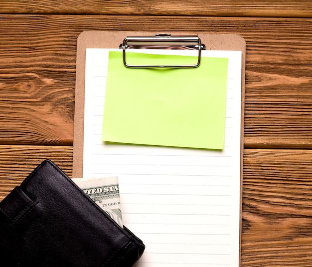 ビジネスと融資の概念。木製のテーブルには、お金が入った財布の横にある空のシートがあります。