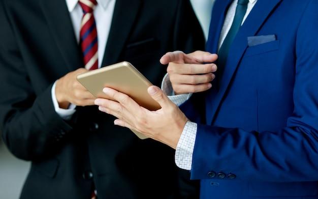 Бизнес и офисная концепция. пара деловых людей в темно-синем костюме и черном костюме с белой рубашкой и галстуком, держа золотую таблетку и указывая на нее на белом фоне. изолированные
