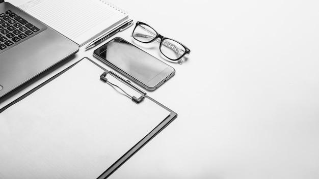 コピー スペースを持つ白い背景にラップトップとスマートフォンを使ったビジネスとオフィスのコンセプト