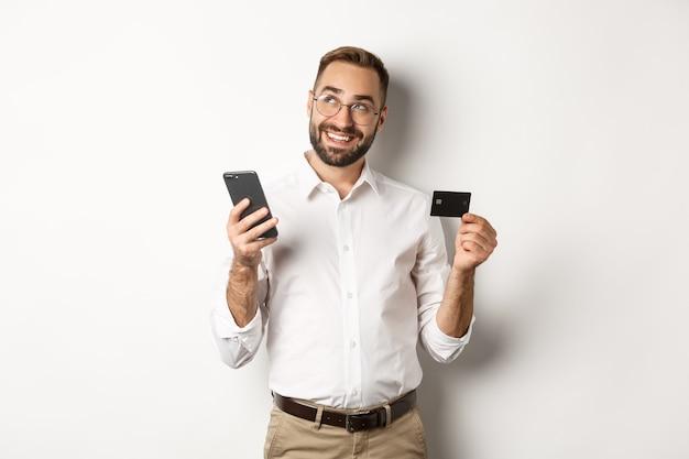 ビジネスおよびオンライン決済。白い背景に立って、クレジットカードとスマートフォンを持って考えているハンサムな男の画像。