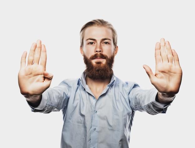 Концепция бизнеса и людей: деловой человек делает знак остановки, студийный снимок
