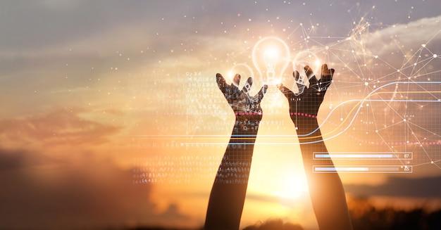 ビジネスと科学メディアの大きなアイデアとインスピレーションデジタルグローバルで電球を握る手