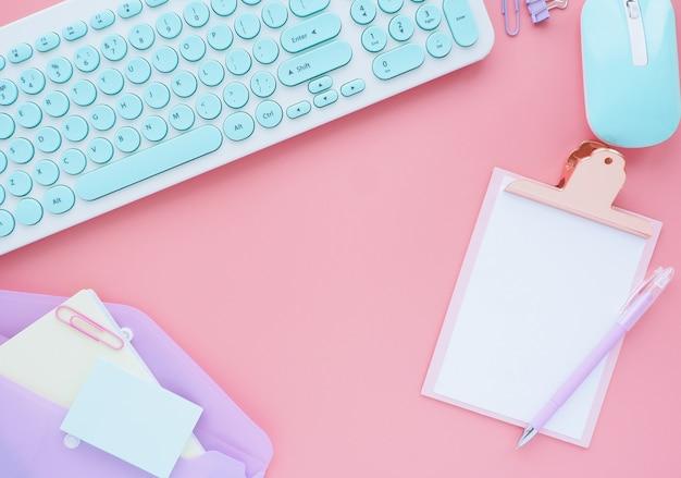 ピンクの背景にビジネスと文房具のアクセサリーがきちんとレイアウトされています。フラットなレイアウト、トップビュー。