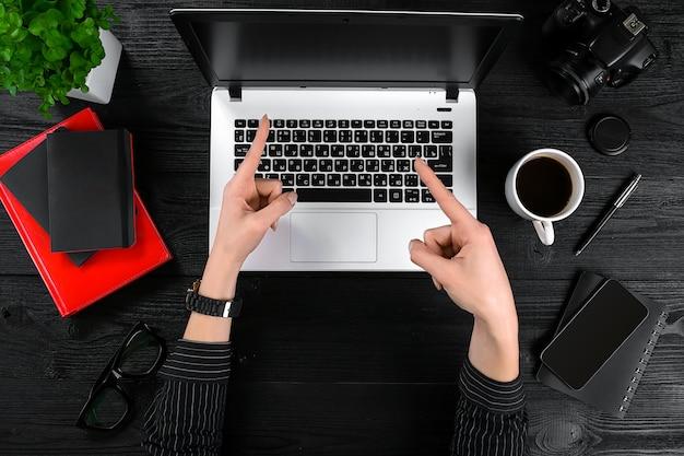 ビジネスとテクノロジーのトピック:デスクで黒と白の背景のラップトップに対してジェスチャーを示す黒いシャツを手に。