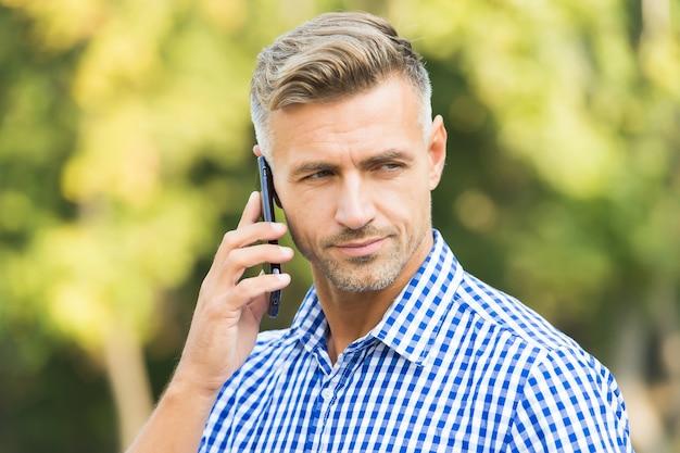 ビジネスアプローチ。現代生活におけるコミュニケーション。アジャイルビジネス。成熟した無精ひげを生やした男のシャツ。屋外の携帯電話で話す男性。外出先で働いているハンサムな男。男性は会話をしています。