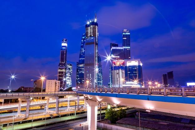 Деловая архитектура - небоскребы и светлые тропы. современный бизнес-центр в ночных огнях