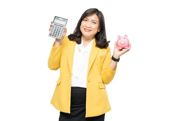 電卓と貯金箱を保持しているビジネスアジアの女性。