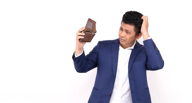 Деловой азиатский мужчина шокирован, удивлен, потерял дар речи, держа пустой бумажник на белом