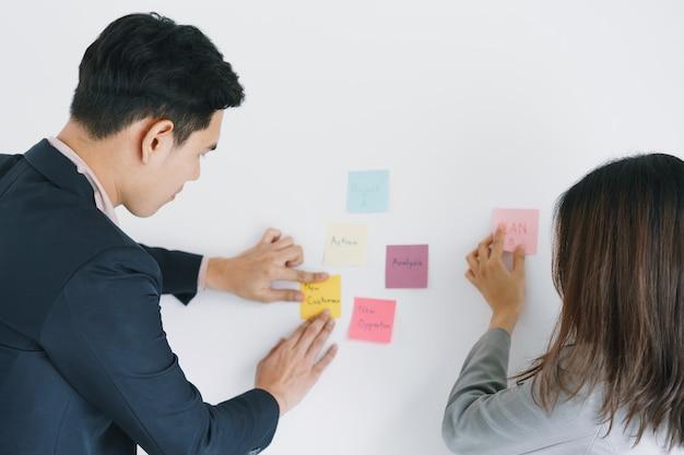 Бизнес азиатские два человека, встречающиеся в офисе и использующие заметки, чтобы поделиться идеей